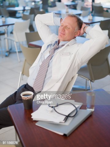 Doctor relaxing in cafeteria : Stock Photo