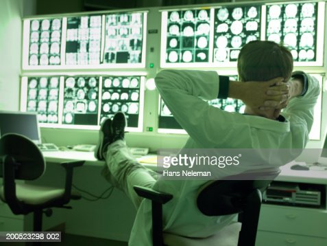 Doctor relaxing with feet up in x-ray laboratory : Stock Photo