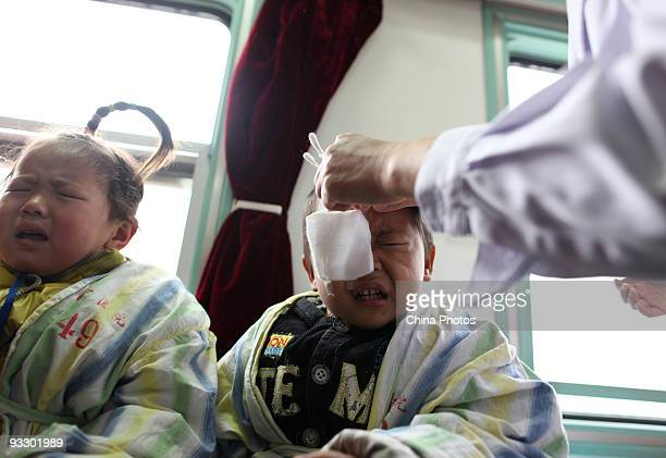 A doctor removes a bandage for a fouryearold boy who has undergone cataract surgery by the Lifeline Express in a hospital on November 22 2009 in...