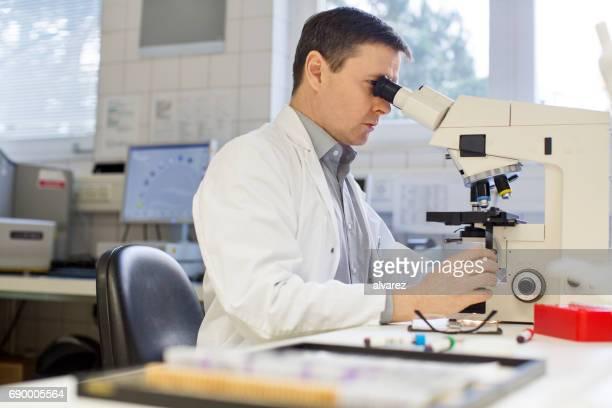 Arzt Untersuchung unter Mikroskop im Krankenhaus