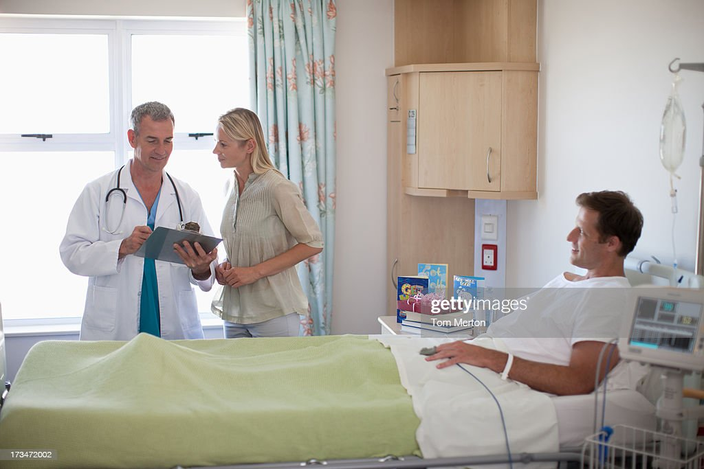 Doctor reviewing medical chart with patient's wife in hospital : Stock Photo
