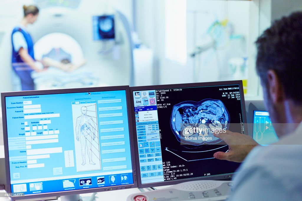 Doctor running CT scan from control room : Stock Photo