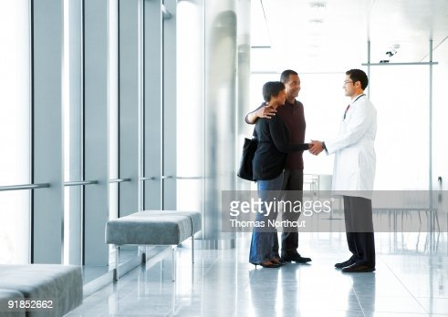 Doctor shaking hands with couple in lobby : Stock Photo