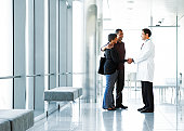 Doctor shaking hands with couple in lobby