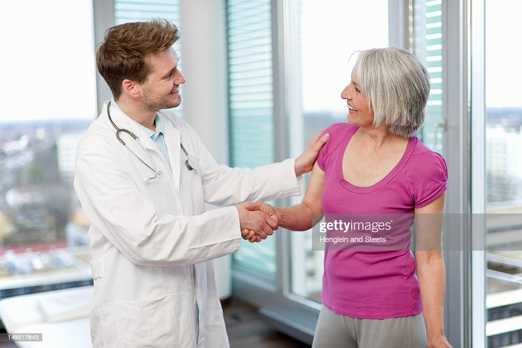 Doctor shaking womans hand in office : Stock Photo