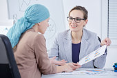 Smiling doctor showing a chart to her cancer patient