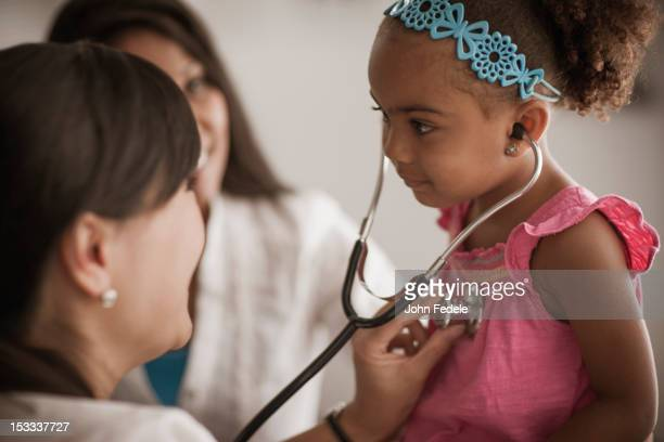 Doctor showing girl how to use stethoscope
