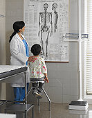 Doctor showing girl (5-7 years) poster in examination room