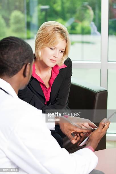 Doctor showing information on a digital tablet