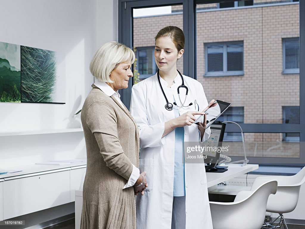 doctor showing patient results on digital tablet
