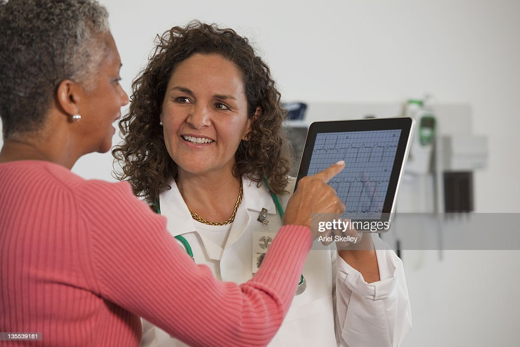 Doctor showing patient test results on digital tablet : Stock Photo
