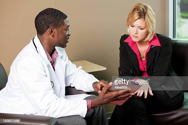 Docteur montrant quelque chose sur une tablette numérique à un patient féminin