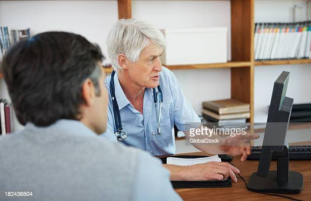 Doctor showing something to his patient on computer