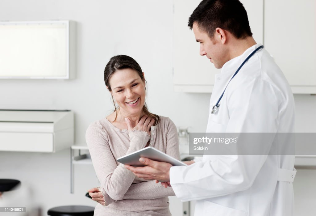 Doctor showing tablet screen to patient : Stock Photo