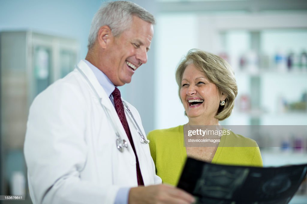 Doctor Showing X-Ray Image To Cheerful Mature Female Patient. : Stock Photo