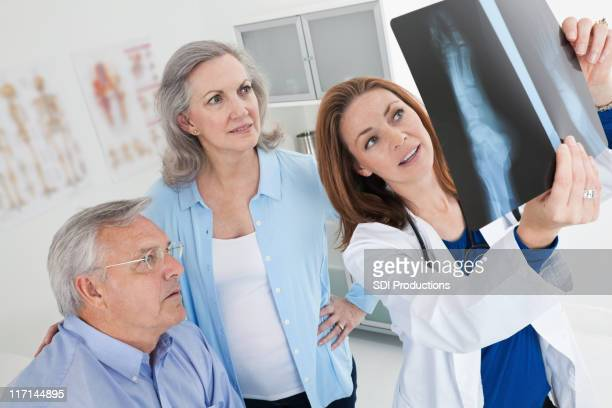 Doctor Showing X-Ray Results to Mature Adult Couple