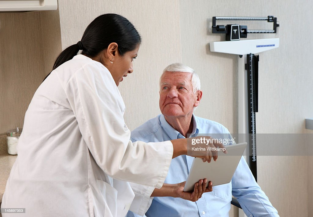 Doctor shows patient information on a tablet. : Stock Photo