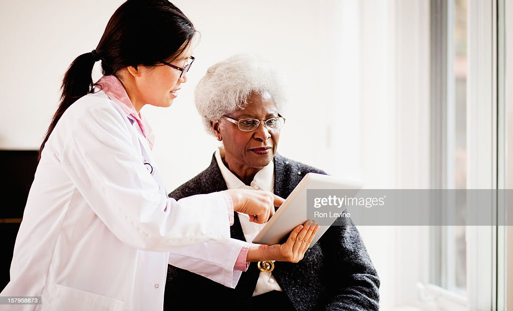 Doctor shows patient information on digital tablet : Stock Photo