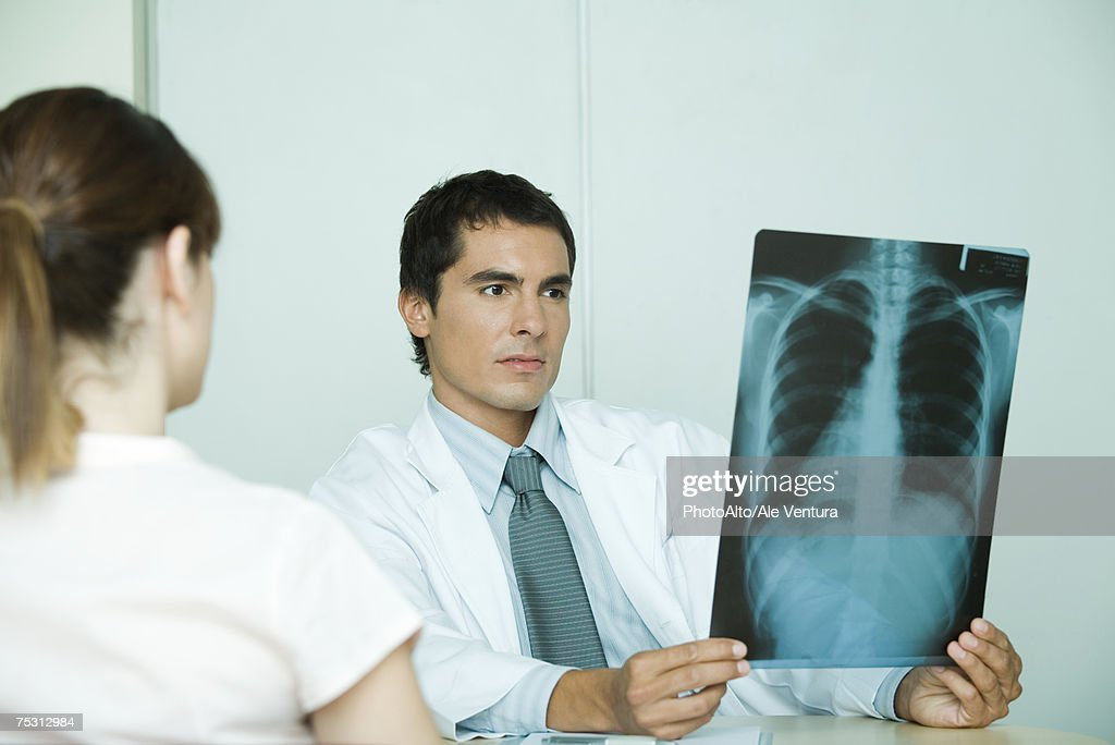 Doctor sitting across from female patient, holding x-ray : Stock Photo
