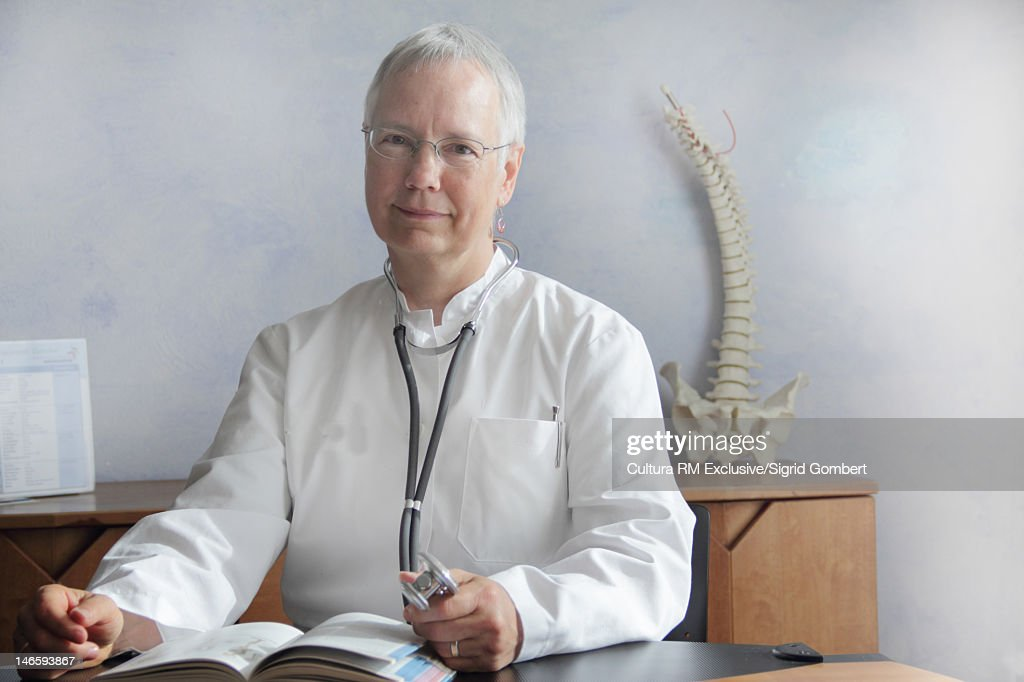 Doctor sitting at desk in office : Stock Photo