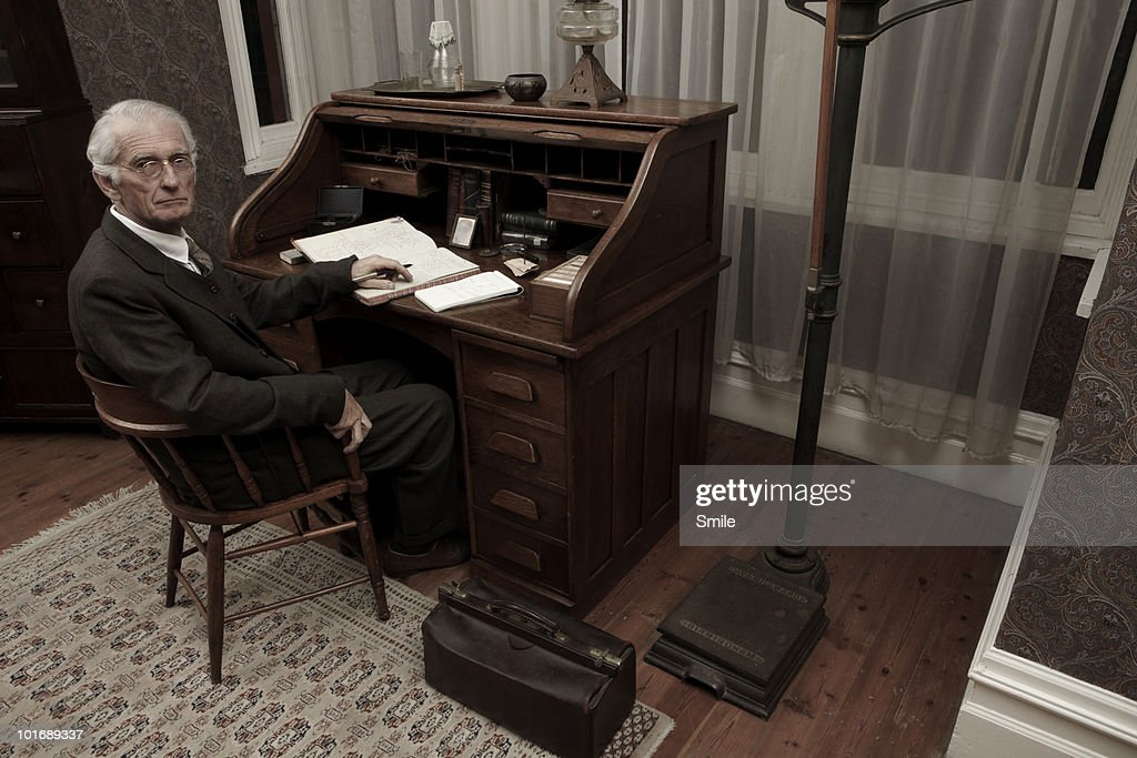 Doctor sitting at his desk : Stock Photo
