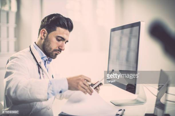 Doctor Sitting in His Office Using Computer