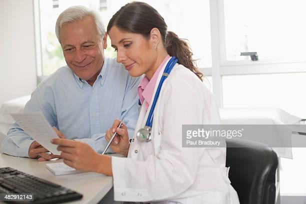Arzt Sitzen im Büro mit Patienten reden und hält Papier