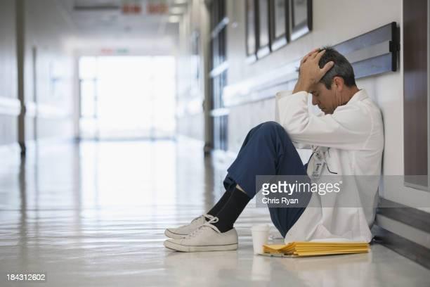 Doctor sitting on floor in hospital corridor with head in hands