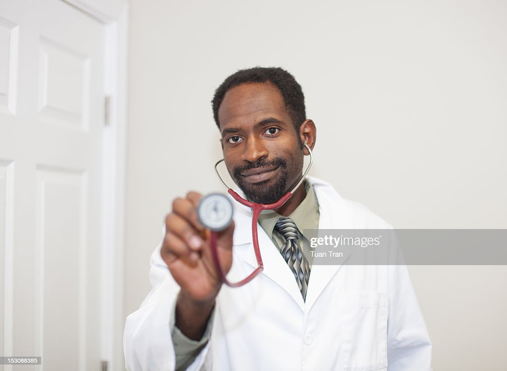 Doctor smiling and looking at camera : Stock Photo