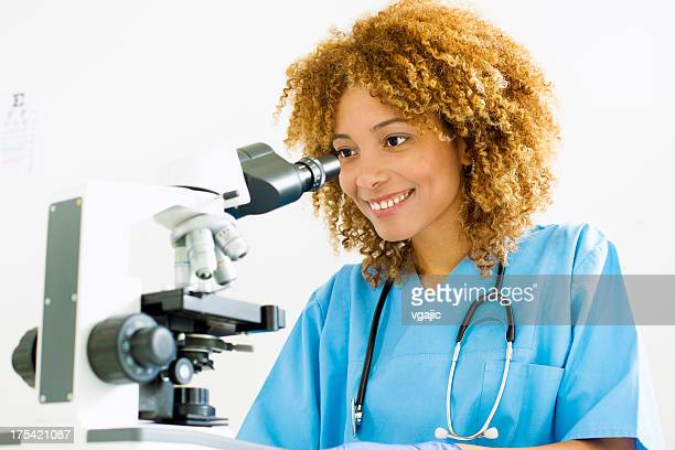 Doctor smiling and looking through microscope.