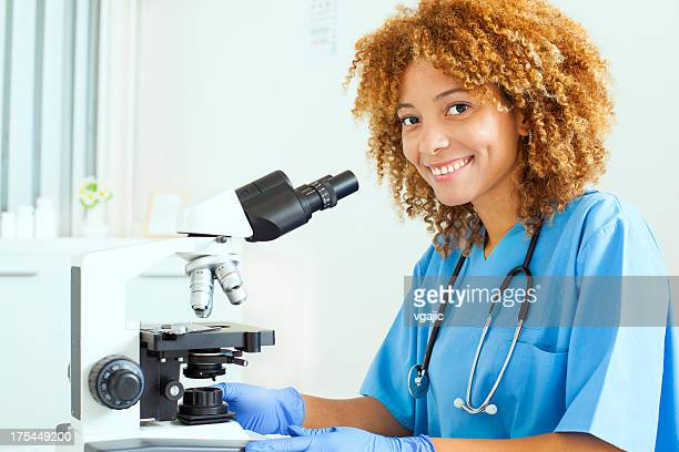 Doctor smiling and working on microscope
