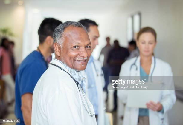Doctor smiling in hospital hallway