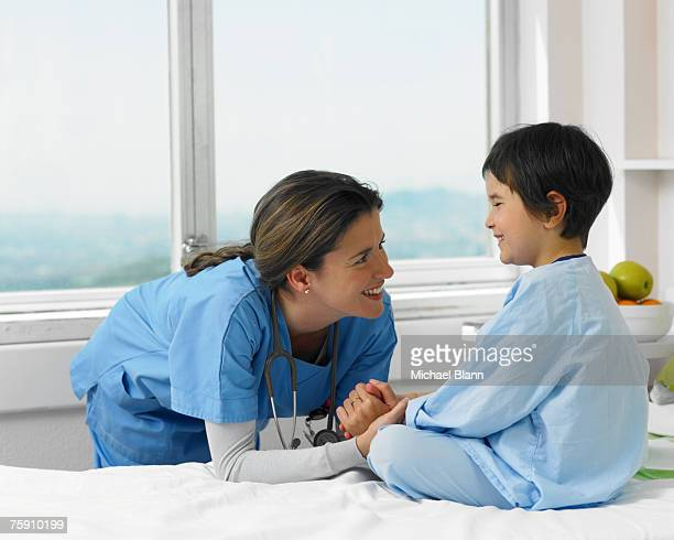 Doctor smiling with patient in hospital bed