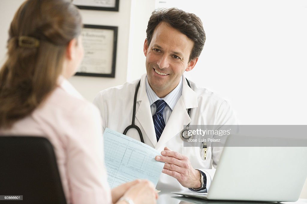 Doctor speaking with female patient : Stock Photo