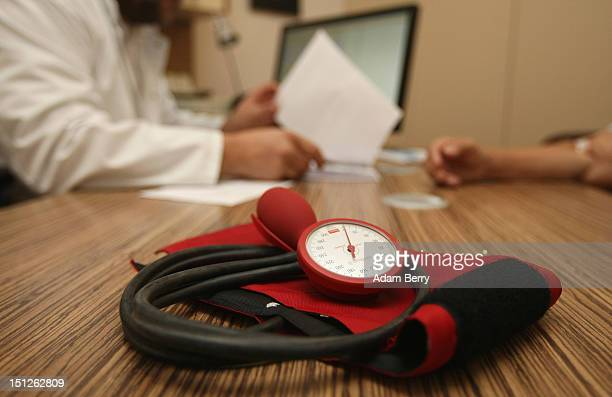 A doctor speaks to a patient as a sphygmomanometer or blood pressure meter lies on his desk on September 5 2012 in Berlin Germany Doctors in the...