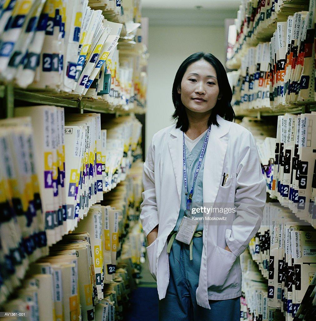 Doctor standing between shelves of medical patient records : Stock Photo