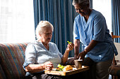 Doctor standing by senior woman eating food at table in nursing home