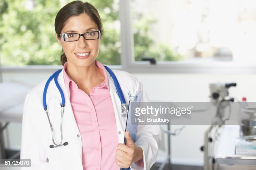 Doctor standing in hospital near large windows holding clipboard and smiling : Stock Photo