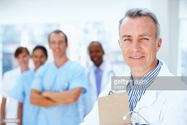 Doctor supported by his staff
