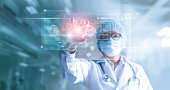 Doctor, surgeon analyzing patient brain testing result and human anatomy on technological digital futuristic virtual computer interface, digital holographic, innovative in science and medicine concept