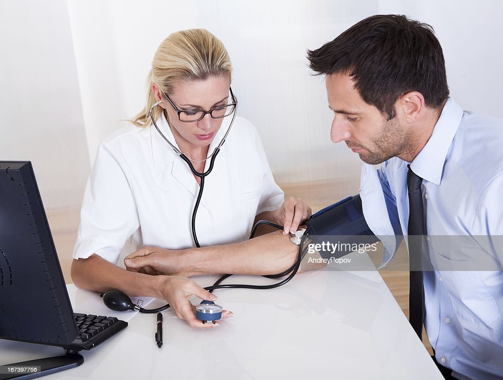 Doctor taking a patients blood pressure : Stock Photo
