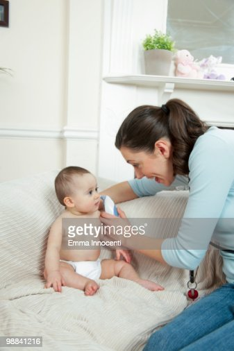 Doctor taking baby ear temperature in living room : Stock Photo