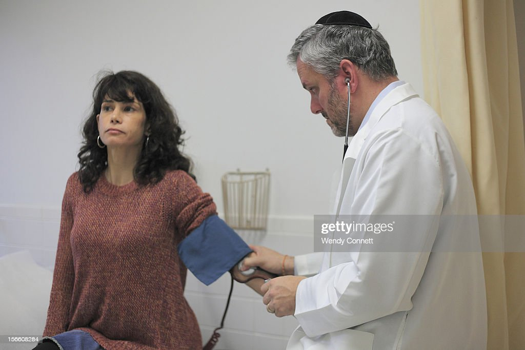 Doctor taking blood pressure : Stock Photo