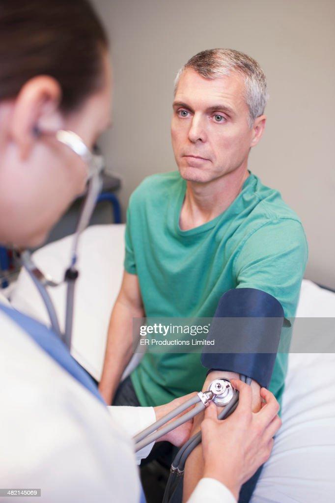 Doctor taking man's blood pressure in hospital