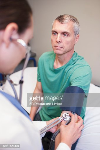 Doctor taking man's blood pressure in hospital