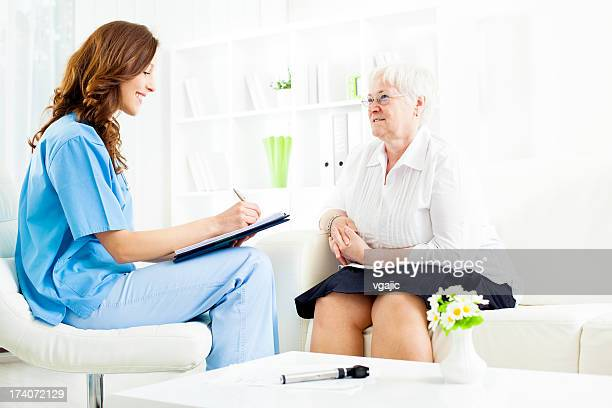 Doctor Taking Notes from Senior Woman patient.
