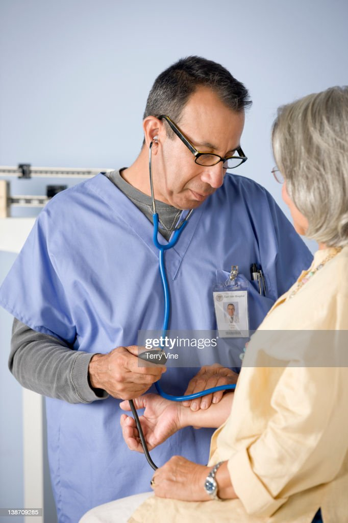Doctor taking patient's blood pressure : Stock Photo