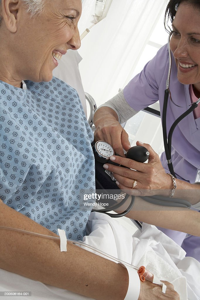 Doctor taking patients blood pressure : Stock Photo