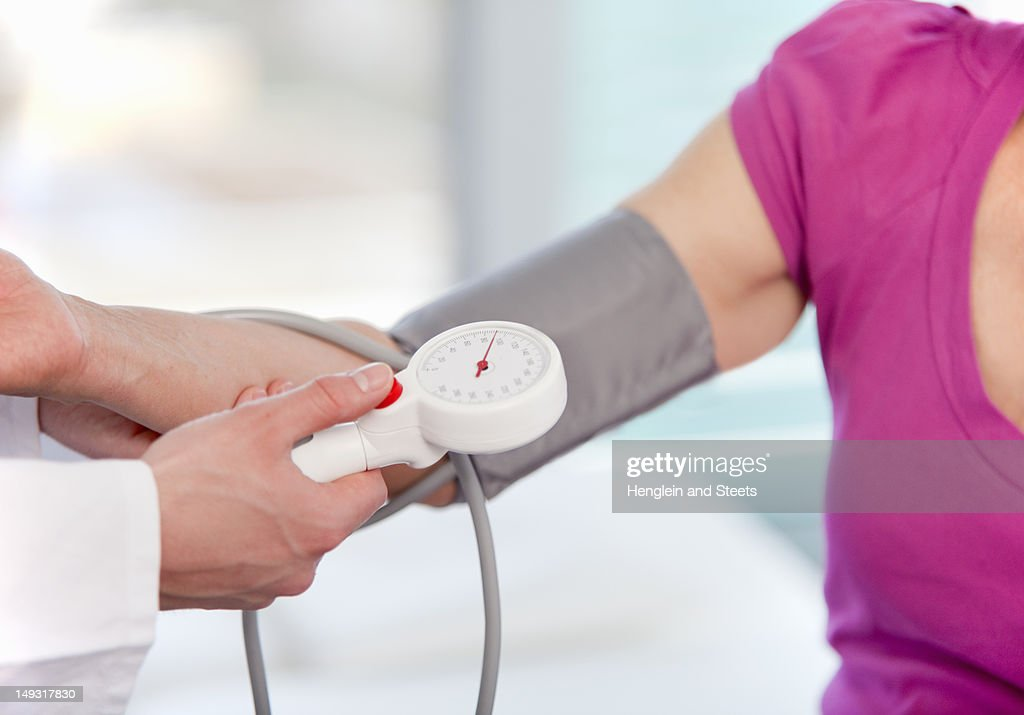 Doctor taking womans blood pressure : Stock Photo
