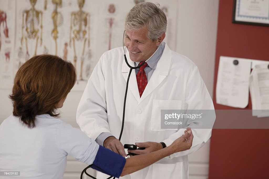 Doctor taking woman's blood pressure